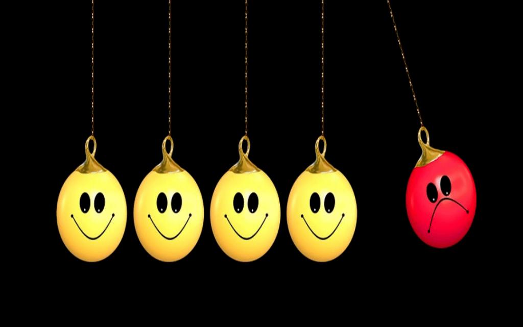 quatro bolas amarelas com sorrisos e uma bola vermelha triste